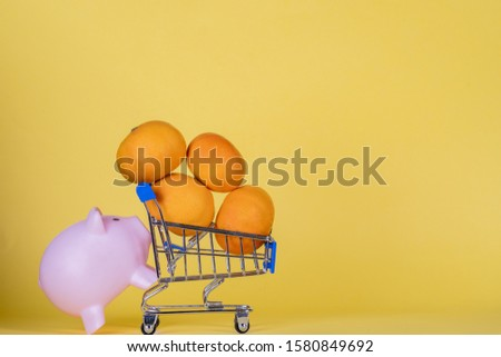 shopping cart with oranges pushed by piggy bank on yellow background #1580849692