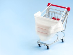 Shopping cart with protective medical mask against coronavirus. Safe and online shopping on quarantine concept. Light blue background, copy space.