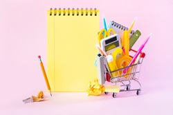 Shopping cart with school supplies on the pink background. Back to school