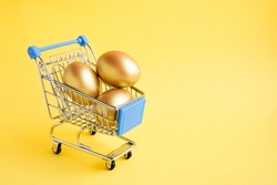 Shopping cart with three golden eggs isolated on yellow background. Easter sale banner. Copy space