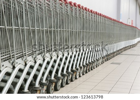 Shopping carts in a row in front of a mall - stock photo