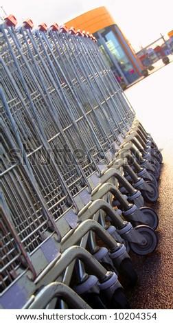 Shopping carts in a row towards entrance of a shopping mall.