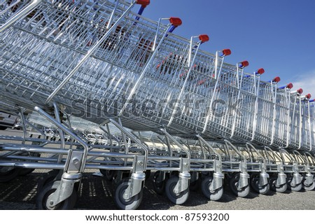 Shopping carts in a stack against a clear blue sky