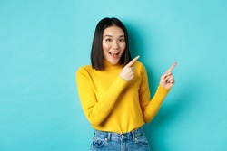 Shopping concept. Beautiful chinese girl in yellow sweater pointing fingers at upper right corner logo banner, smiling amused, standing over blue background
