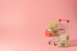 Shopping concept : Cartons or Paper boxes in red shopping cart on pink background. online shopping consumers can shop from home and delivery service. with copy space