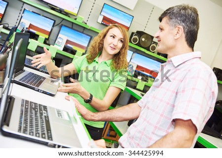 Shopping concept. Happy seller assistant woman help purchaser choosing notebook computer in electronics supermarket shop #344425994