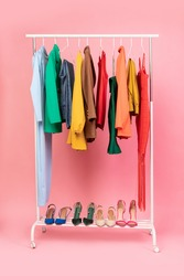 Shopping Concept. Vertical Shot Of Clothing Rail With Bright Trendy Clothes Hanging On Hangers And Shoes Over Pink Studio Background In Empty Room. Fashion Trends And Style Concept