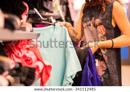 Shopping concept - woman choosing dress during shopping at garments apparel clothing shop