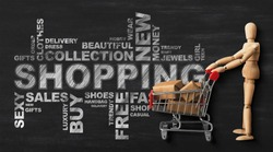 Shopping Conceptual Wordcloud With Wooden Man And Buyer's Shopper Cart Over Black Chalkboard Background. Panorama