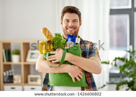 shopping, consumerism and people concept - smiling young man with food in bag at home