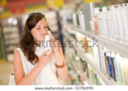 Shopping cosmetics - woman smelling bottle of shampoo in supermarket