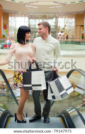 Shopping couple at the escalators with bags