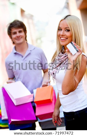 Shopping couple with bags paying with a debit or credit card