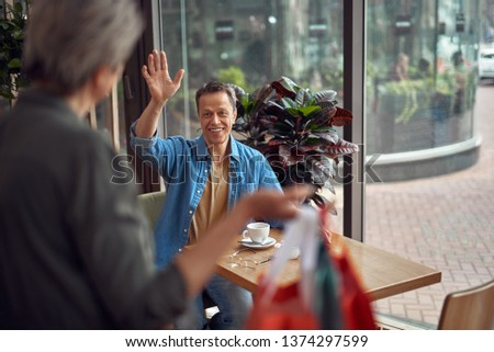 Shopping day. Waist up portrait of smiling aged male sitting in cafe and saluting to lady coming with many shop packages