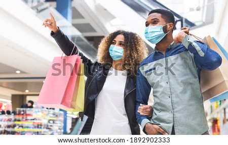 Shopping during quarantine concept. Young african american couple doing shopping together in city mall, wearing protective face masks, panorama. Black lady showing her boyfriend new store, copy space ストックフォト ©