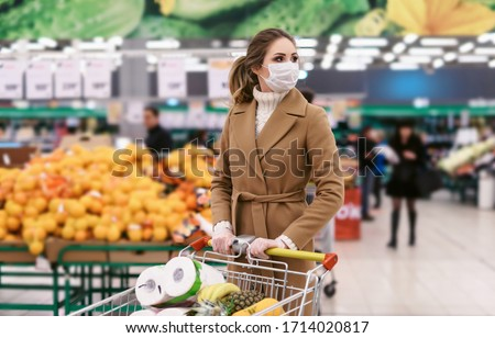 Shopping during the coronavirus Covid-19 pandemic. A young woman buys food in a supermarket with shopping cart. Woman in facial mask and gloves to prevent infection.