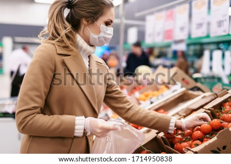 Shopping during the coronavirus Covid-19 pandemic. A young woman buys tomatoes in a supermarket. Woman in facial mask and gloves to prevent infection.