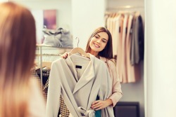 shopping, fashion, clothes, style and people concept - happy woman trying coat on in mall or clothing store