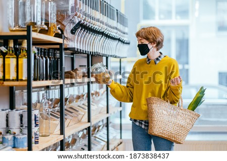 Shopping, food, sale, consumerism concept. Blond short haired woman in face protective mask holds glass jar with soya, buying at grocery store Reusable wicker basket for shopping. Zero waste concept. Foto d'archivio ©