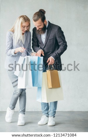 shopping for christmas presents and sharing emotions concept. woman showing purchase to a man holding multiple bags.