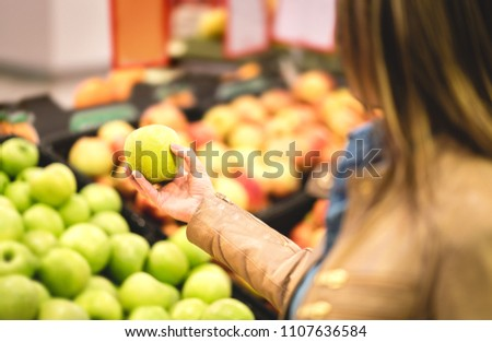 Shopping for fruit and healthy food in supermarket. Fitness lady on organic diet doing groceries. Woman buying, holding and choosing fresh apple in grocery store.