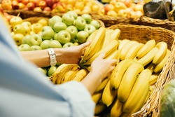 Shopping for groceries, close-up female hands take fresh bananas from store shelf.