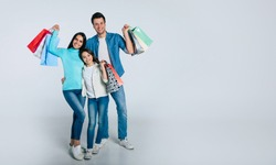 Shopping forever. Full-length photo of mom, dad, and daughter, who are hugging, looking in the camera with happy facial expressions and showing multicolored paper bags in their hands.