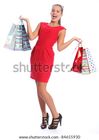Shopping gift bags held by beautiful sexy young woman with lovely happy smile, wearing black high heeled shoes and short red dress. She has blond brown hair and sunglasses.