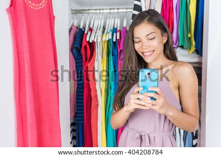 Shopping girl taking selfie in mirror of changing room at store or home walk-in closet in bedroom. Asian woman taking a photo of her outfit texting sms on social media using smart phone fashion app.