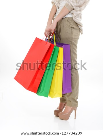 shopping girl, young woman on high heels with colored shopping bags, legs detail over white