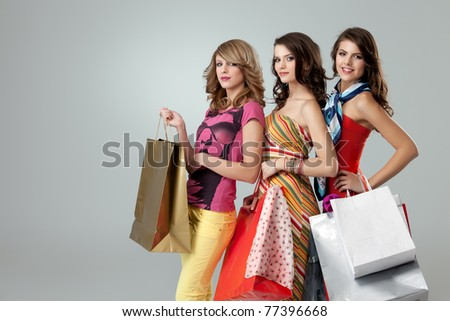 shopping girlfriends posing happy at camera