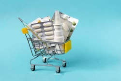 Shopping grocery cart with medicament, tablet, spray, thermometer on blue background. Concept of healthy care, business, shopping, sales.
