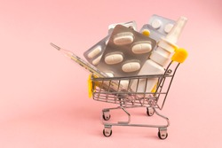 Shopping grocery cart with medicament, tablet, spray, thermometer on pink background. Concept of healthy care, business, shopping, sales.
