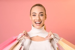 Shopping. Happy Woman Holding Colorful Shopper Bags Posing On Pink Background. Studio Shot