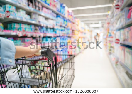 Shopping in supermarket a shopping cart view with motion blur.Close up of a woman shopping in a supermarket.Customer pushing a shopping cart in a supermarket.