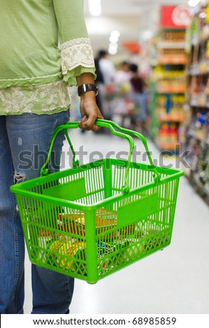 shopping in supermarket, carrying a grocery basket