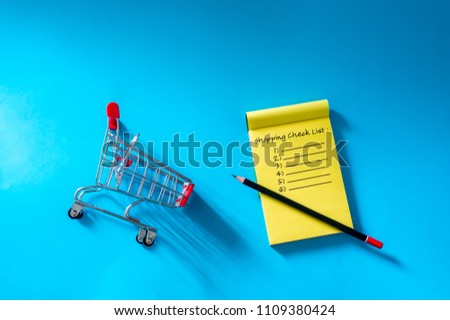 Shopping list before going to buy the groceries. Top view trolley and notes isolated on blue background.