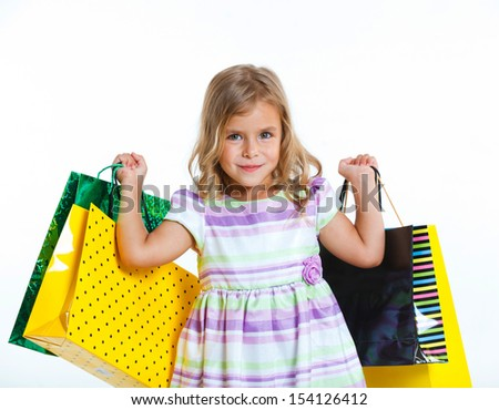 Shopping little girl happy smiling holding shopping bags isolated on white background.
