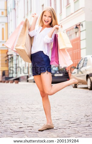 Shopping makes me happy! Full length of attractive young cheerful woman holding shopping bags and looking at camera while standing outdoors