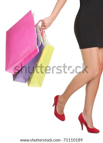 Shopping on white background. Closeup of woman holding shopping bags wearing red high heels.