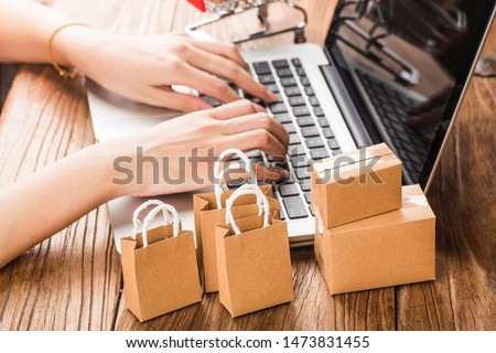 shopping online at home concept.Cartons in a shopping cart on a laptop keyboard.online shopping is a form of electronic commerce that allows consumers to directly buy goods from a seller over internet