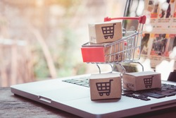 Shopping online. cardboard box with a shopping cart logo in a trolley on laptop keyboard. Shopping service on The online web. offers home delivery