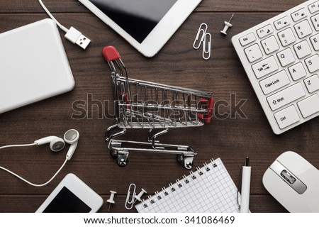 shopping online concept. small red trolley and gadgets on the table