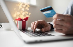 Shopping online during holidays. Man using laptop computer and credit card, ordering Christmas gifts. Shopping, internet banking, store online, payment, surprise, spending money, holidays concept