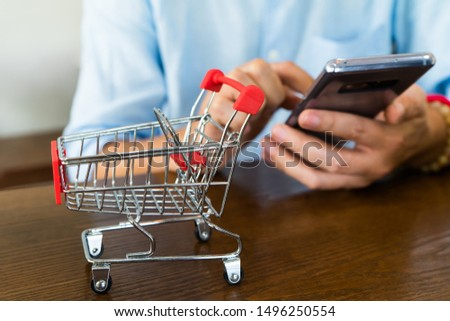 Shopping online.Pushcart or shopping trolley basket with man use telephone or smartphone to search information for sale and buy.