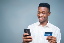 Shopping online with his Mobile phone holding a credit card smiling
