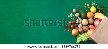 Shopping or delivery healthy food background. Healthy vegan vegetarian food in paper bag vegetables and fruits on green, copy space. Food supermarket and clean vegan eating concept.
