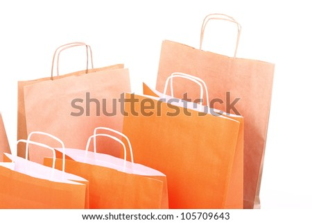 Shopping orange gift bags isolated on white background
