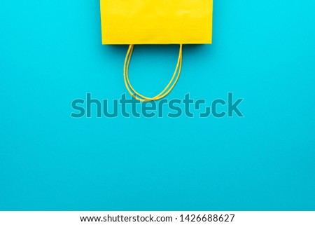 shopping paper bag on the blue background with copy space. flat lay photo of upturned yellow bag. summer sale concept