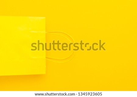 shopping paper bag on the yellow background with copy space. flat lay photo of upturned yellow bag. summer sale concept